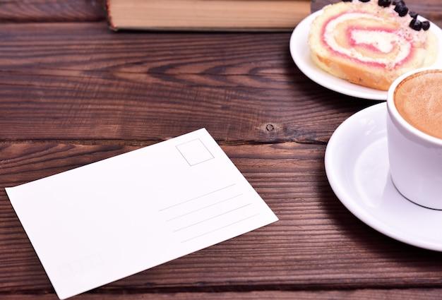 Leere weißbuchkarte auf dem tisch, seitliche espressotasse