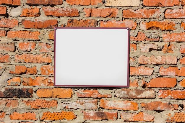 Leere weiße anschlagtafel auf der alten orange backsteinmauer. attrappe, lehrmodell, simulation.