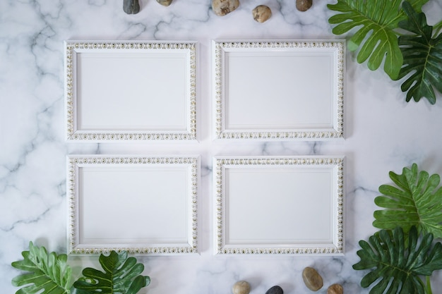 Leere weiße bilderrahmen und grünes blatt auf marmorhintergrund.
