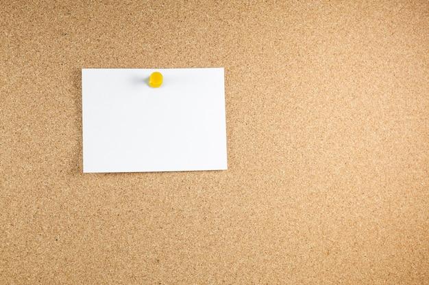 Leere weiße briefpapiere werden an eine korkplatte geheftet.