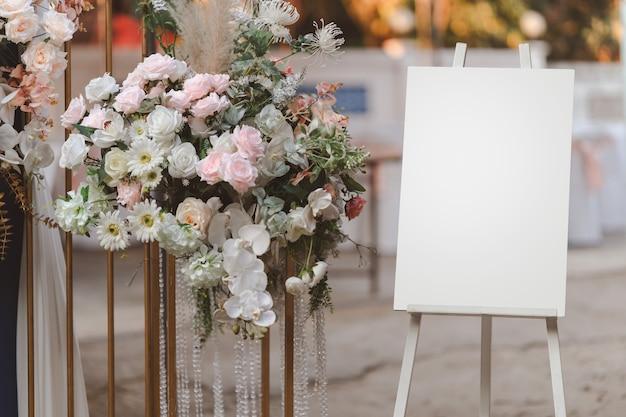 Leere weiße fotoanzeigetafel auf ständer für hochzeitsbogen