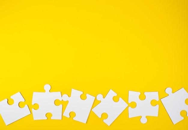 Leere weiße große puzzlespiele auf gelbem hintergrund, ebenenlage