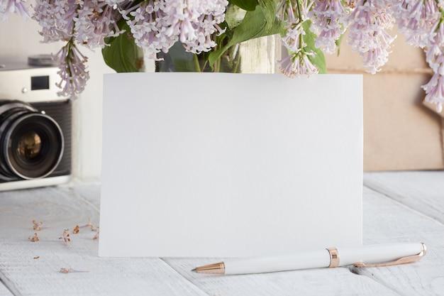 Leere weiße grußkarte mit flieder blüht blumenstrauß.