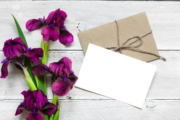 Leere weiße grußkarte mit lila irisblumenstrauß und umschlag auf weißem hölzernem hintergrund