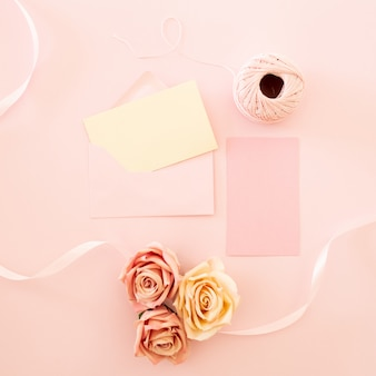 Leere weiße grußkarte mit rosa rose blumen blumenstrauß und umschlag mit blütenknospen