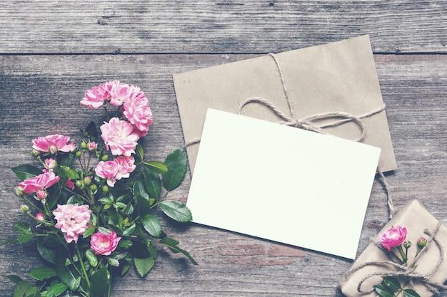 Leere weiße grußkarte mit rosa rosenblumenstrauß und umschlag mit geschenkbox
