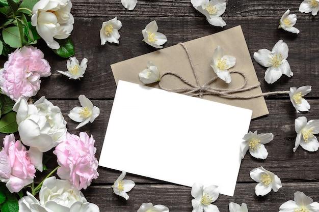 Leere weiße grußkarte mit rosa und weißen rosen im rahmen aus jasminblüten