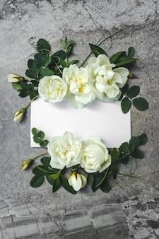 Leere weiße grußkarte mit weißem rosenblumenstrauß, blumenrahmen. kreativer gruß. schöne blumen und leere karte. romantische hochzeitseinladung. geschenk für frauen.