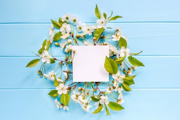 Leere weiße grußkarte mit weißen frühlingsblumen auf blauem hölzernem hintergrund. ansicht von oben.