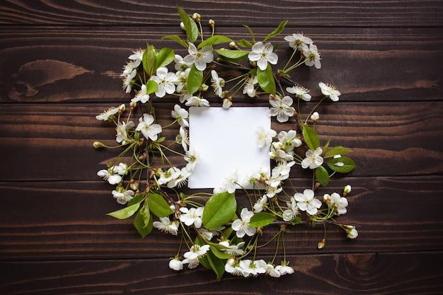 Leere weiße grußkarte mit weißen frühlingsblumen auf hölzernem hintergrund. ansicht von oben.
