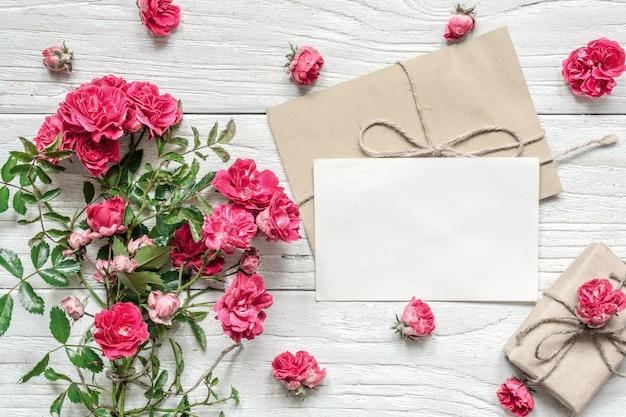 Leere weiße grußkarte und geschenkbox mit rosarose blüht blumenstrauß
