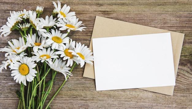 Leere weiße grußkarte und umschlag mit kamillenblumen