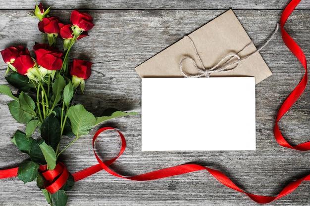 Leere weiße grußkarte und umschlag mit roten rosenblumen und rotem band