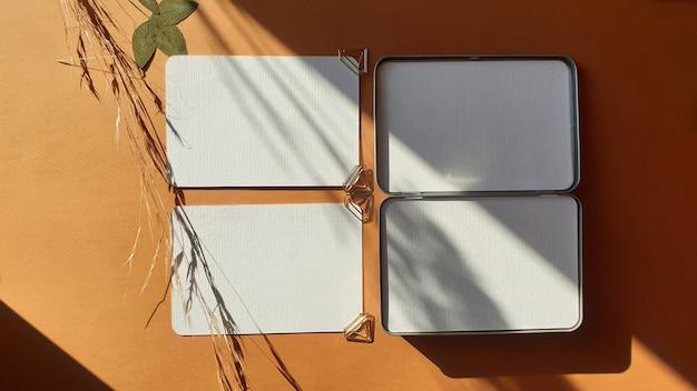 Leere weiße hochzeits-gruß-einladungskartenmodelle mit getrockneten blättern von pflanzen und von kräutern auf strukturiertem terrakottatabelle backgound. elegante moderne vorlage für die markenidentität. flachgelegt, draufsicht