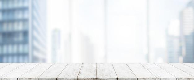 Leere weiße hölzerne tischplatte und unschärfeglasfensterwand-gebäudefahne verspotten herauf hintergrund