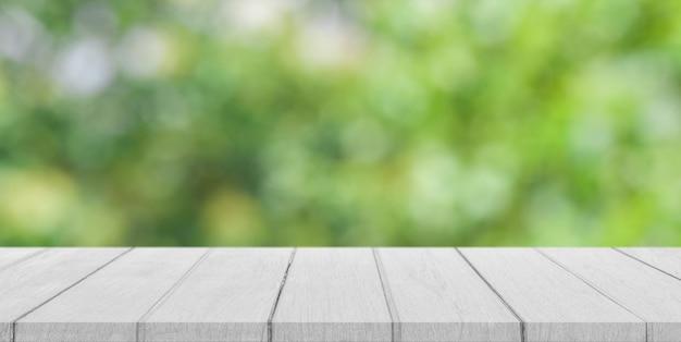 Leere weiße holztischplatte mit unscharfem grünem bokehhintergrund.