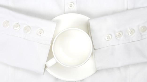 Leere weiße kaffeetasse und untertasse auf einem weißen hemd. bürokleidung und frühstück