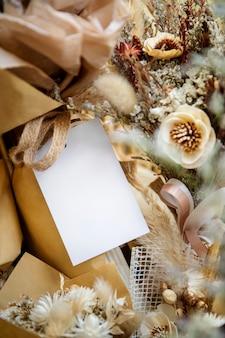 Leere weiße karte auf einem strauß trockener mohnblumen