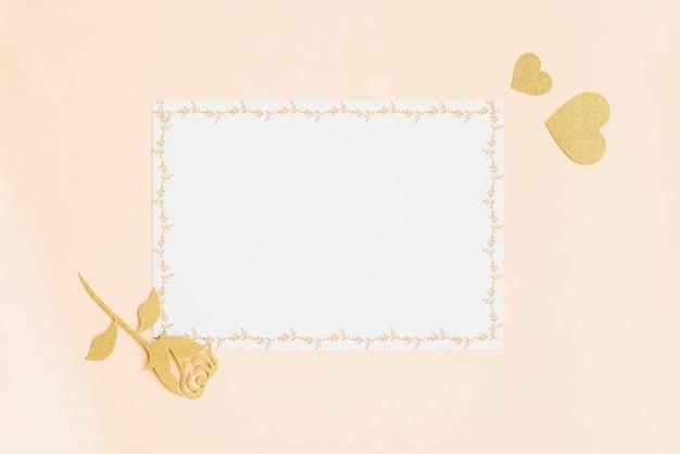 Leere weiße karte mit goldenem herzen und stieg auf farbigen hintergrund