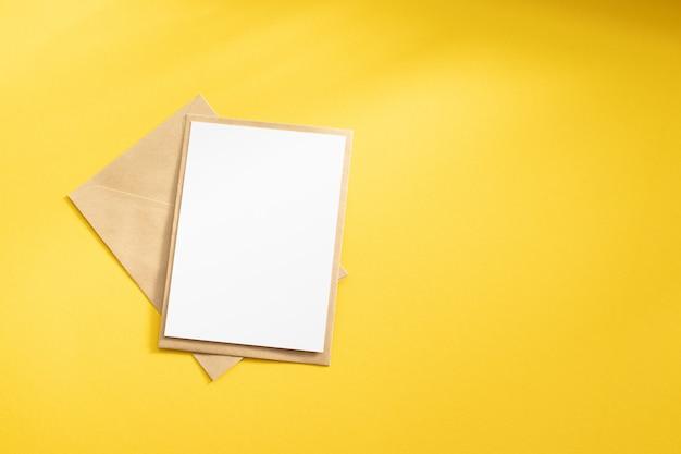 Leere weiße karte mit umschlagschablonenspott des braunen papiers des kraftpapiers oben auf gelbem hintergrund