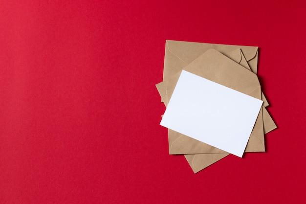 Leere weiße karte mit umschlagschablonenspott des braunen papiers des kraftpapiers oben auf rotem hintergrund