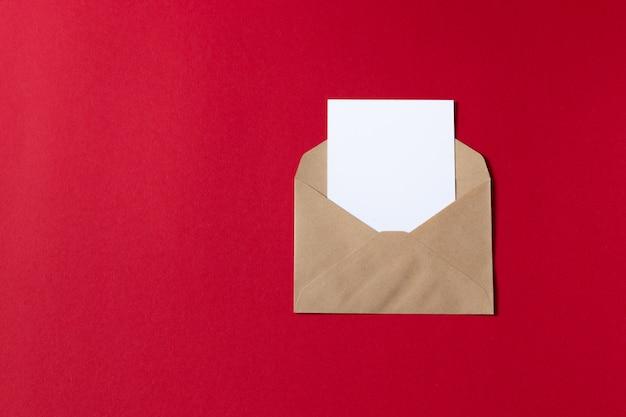 Leere weiße karte mit umschlagschablonenspott des kraftpapiers braunem papier oben