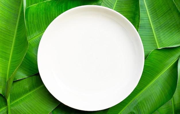 Leere weiße keramikplatte auf bananenblatthintergrund. draufsicht