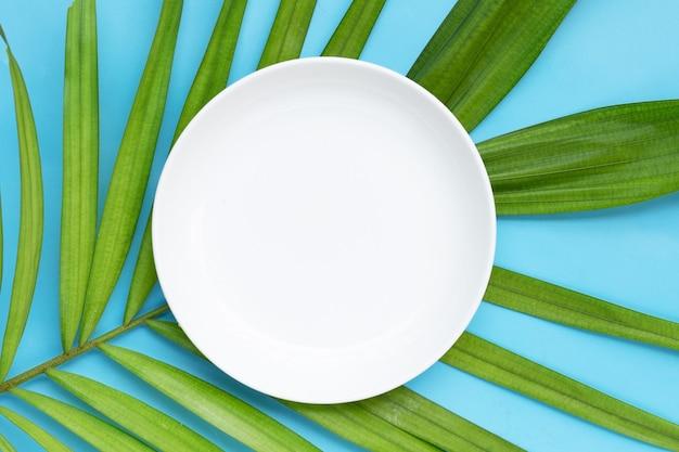Leere weiße keramikplatte auf tropischen palmblättern auf blauem hintergrund. ansicht von oben