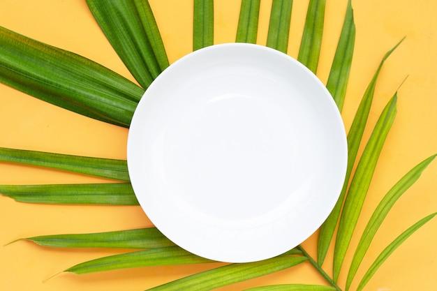 Leere weiße keramikplatte auf tropischen palmblättern auf gelbem hintergrund. ansicht von oben