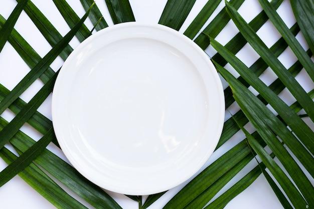 Leere weiße keramikplatte auf tropischen palmblättern auf weißem hintergrund. draufsicht