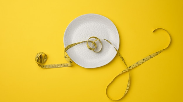 Leere weiße keramikplatte und maßband auf gelbem hintergrund. gesundes ernährungskonzept, gewichtsverlust