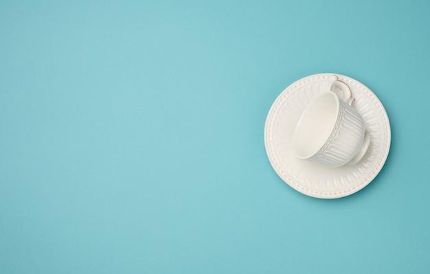 Leere weiße keramiktasse und untertasse auf blauem hintergrund, ansicht von oben
