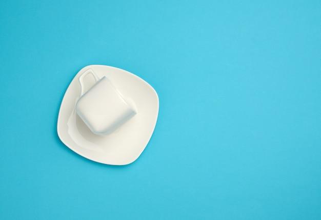 Leere weiße keramiktasse und untertasse auf blauem hintergrund, draufsicht, kopierraum