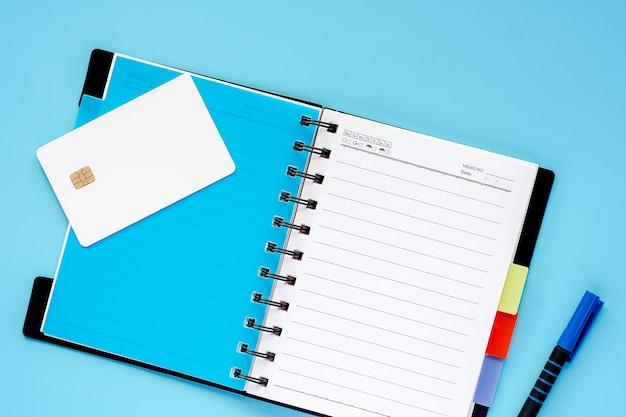 Leere weiße kreditchipkarte, gewundenes notizbuch und ein stift auf blauem hintergrund für das ausgeben von pl