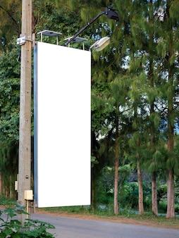 Leere weiße leere fahne auf strommast für werbung neben der straße nahe dem baum und dem grünen garten