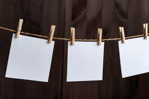 Leere weiße leere quadratische papierkarten mit wäscheklammern am seil
