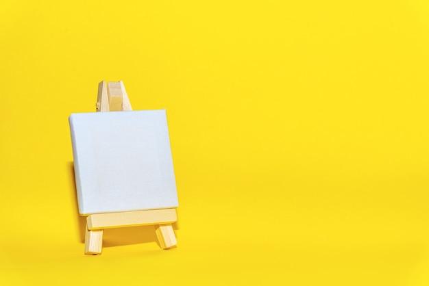 Leere weiße leinwand der hölzernen staffelei auf gelbem hintergrund