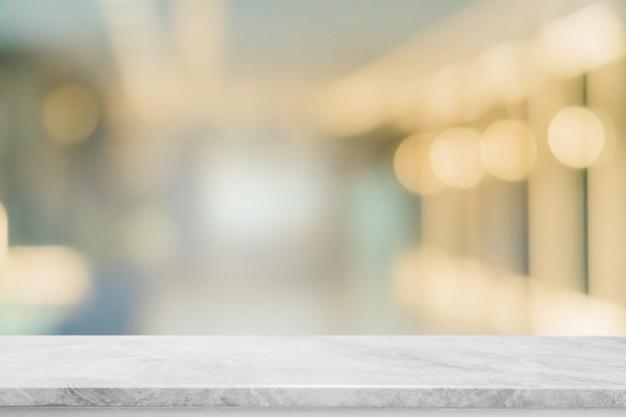 Leere weiße marmorstein-tischplatte und verwischen glasfenster-innenrestaurant-banner verspotten abstrakten hintergrund