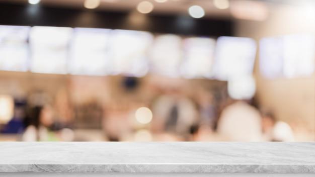 Leere weiße marmorsteintischplatte an verwischt mit bokeh caféinnenraumhintergrund.