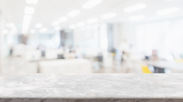 Leere weiße marmorsteintischplatte und unschärfeglasfensterwand im bürogebäude-rauminnenraum