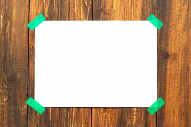 Leere weiße papiernotiz auf brauner holzwand. abstrakter hintergrund.