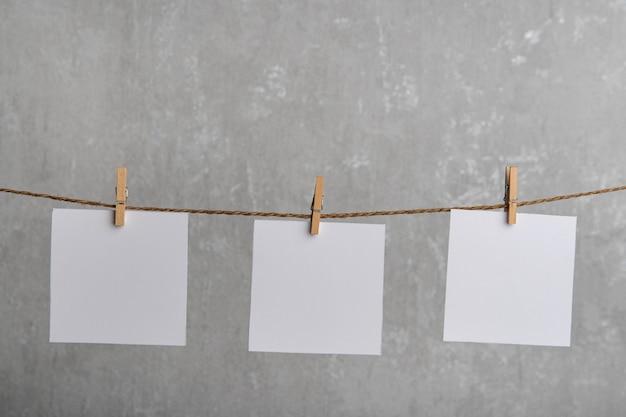 Leere weiße papiernotizen hängen mit wäscheklammern am seil