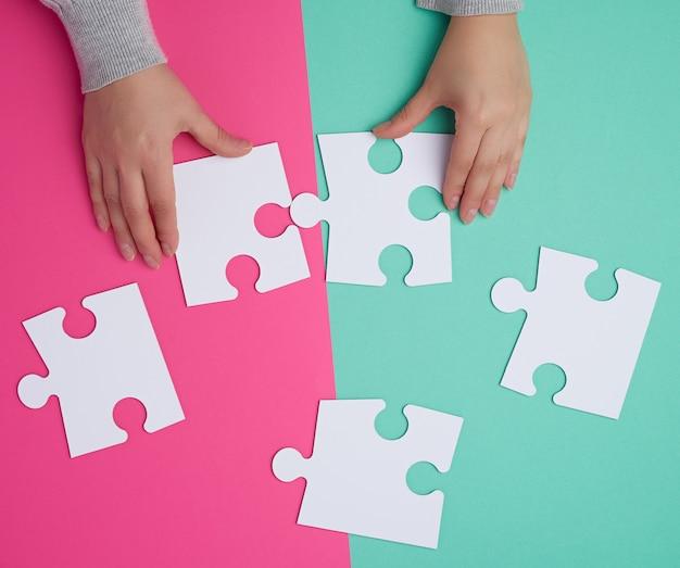 Leere weiße papierstücke puzzlespiele in den weiblichen händen, puzzlespiel angeschlossen