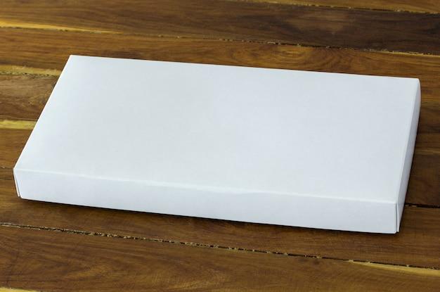 Leere weiße pappverpackungsbox auf dunklem holztisch