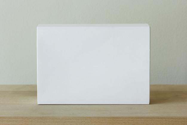 Leere weiße pappverpackungsbox auf holztisch