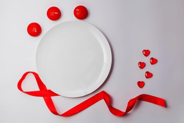 Leere weiße platte auf dem tisch mit rotem band, herzen und kerzen.