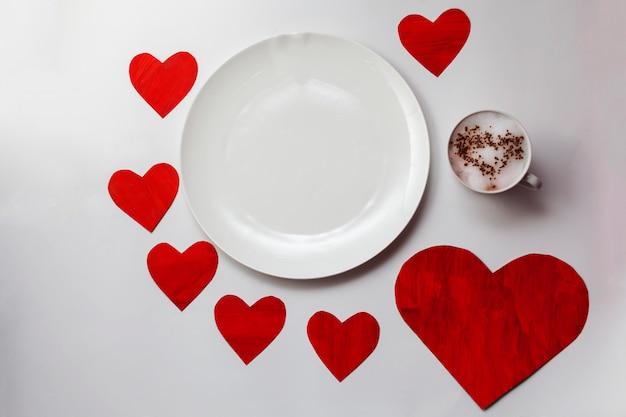 Leere weiße platte auf dem tisch mit roten herzen herum und schale mit einem heißen getränk und einem gemalten herzen auf schaum.