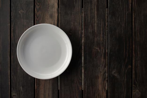 Leere weiße platte auf einem hölzernen dachbodentisch. hochwertiges foto