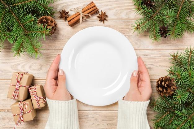 Leere weiße platte auf holzoberfläche mit weihnachtsdekoration