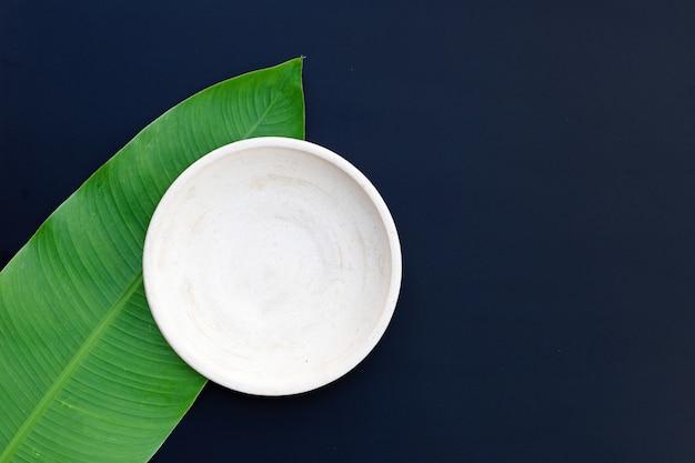 Leere weiße platte auf tropischen bananenblättern auf dunkelheit